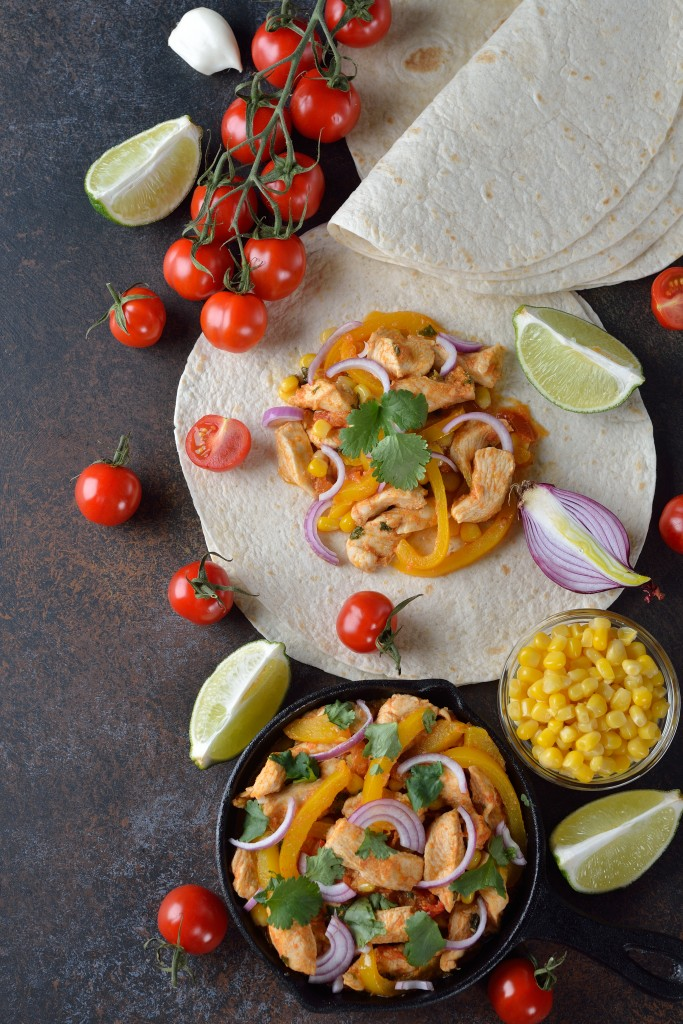 Fajita with chicken and yellow pepper on a brown background