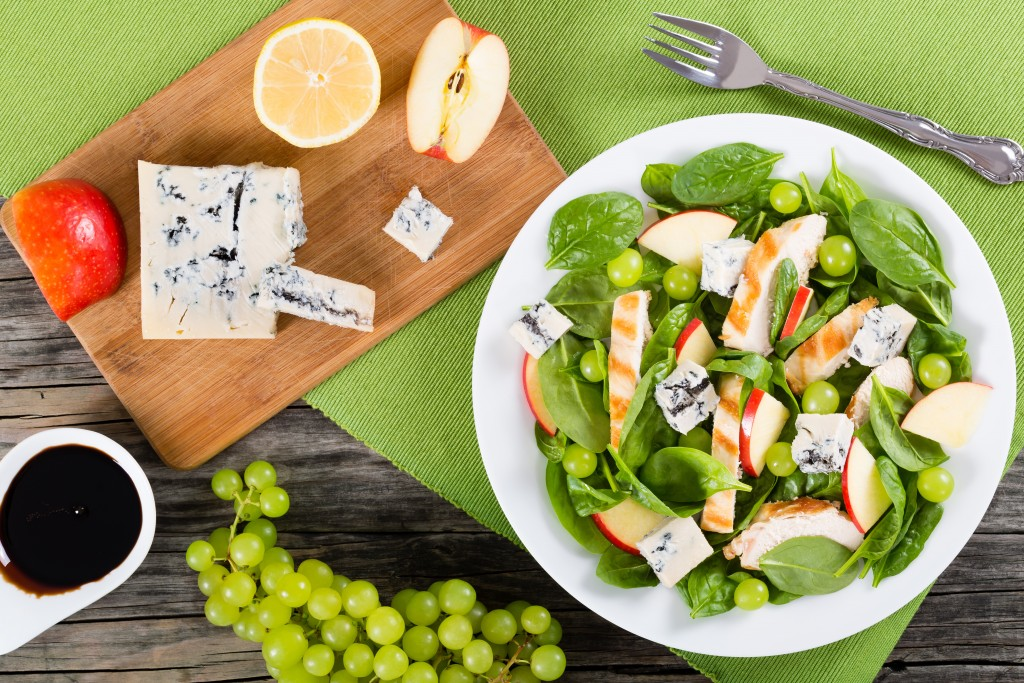 grilled chicken breast, grapes, spinach,  cheese and apple salad on a white dish, on a table mat, cutting board with pieces of apple, lemon and blue cheese, view from above